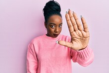 Young African American Woman Wearing Casual Winter Sweater Doing Stop Sing With Palm Of The Hand. Warning Expression With Negative And Serious Gesture On The Face.
