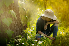 Boy Scout With Hat, Observing In Great Detail, Plants And Insects Of Nature. Boy In Idyllic Jungle-like Landscape