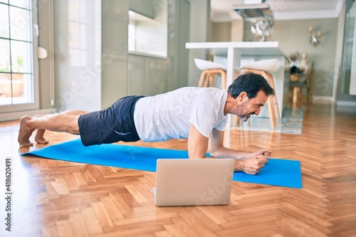 Obraz Middle age man with beard training and stretching doing exercise at home looking at sport video on computer - fototapety do salonu