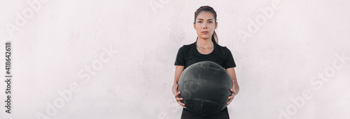 Fotografija Woman athlete cross training carrying throwing heavy medicine ball doing squats and ball slam