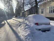 Cars Are Covered In Snow On A Cold And Sunny Winter Day In An Idyllic Suburb With Wooden Houses.