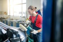 Smiling Repairman Grinding Car Body In Garage