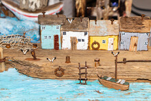 Colorful Old Miniature Wooden Houses Stand On The Embankment Of The Sea Or River. Fishing Nets. The Boat Is Moored To The Shore. The Village Of Fishermen.