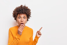 Horizontal Shocked Speechless Woman With Afro Hair Keeps Jaw Dropped Indicates Away On Blank Space Says Check Out Something Unusual Wears Long Sleeved Orange Jumper Isolated Over White Background