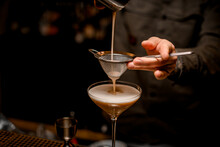 Close-up On Sieve Through Which Male Bartender Pours Frothy Espresso Martini Cocktail Into Glass