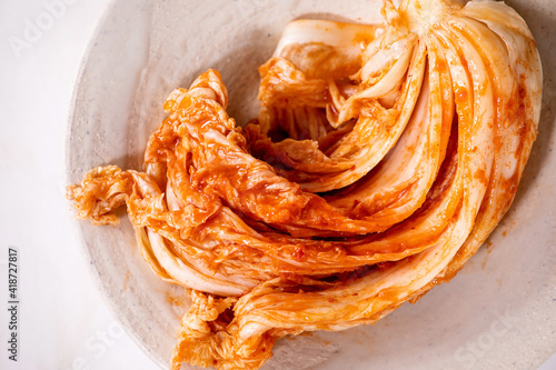 Photo Homemade korean traditional fermented appetizer kimchi cabbage served in ceramic plate over white marble background