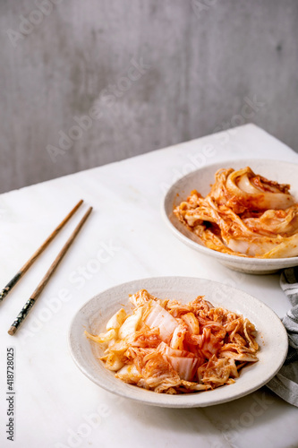 Homemade korean traditional fermented appetizer kimchi cabbage whole and chopped served in ceramic plate with chopsticks over white marble table Fototapet