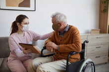 Portrait Of Young Nurse Assisting Senior Man In Wheelchair Using Digital Tablet At Retirement Home, Both Wearing Masks, Copy Space