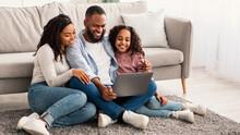 Happy Black Family Using Laptop In Living Room