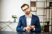 Young Stately Male Freelancer Sitting At Desk In Office, Interviews, Talking At Camera, Leader Of The Team, Explaining His Position Or Idea, Conducts Business Training, Sharing His Experience