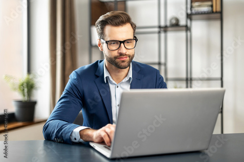 Photo Relaxed man working at contemporary office, typing on keyboard, sitting on comfy