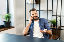 Image Of Handsome Businessman Talking On Cell Phone While Working At The Desk In Trendy Office With Green Plants In The Background, Making An Important Deal, Communicating With Colleagues Or Partners