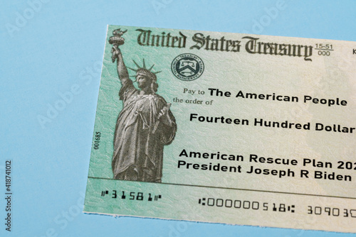 US Treasury illustrative check to illustrate American Rescue Plan Act of 2021 payment on blue background © steheap