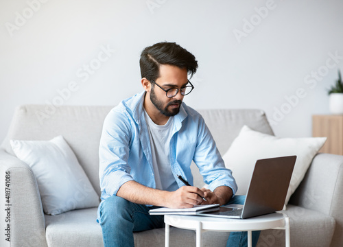 Online Education. Young Eastern Man Study With Laptop At Home, Taking Notes