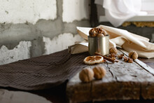 Walnuts In A Tin Of Yellow Metal Next To The Shell And The Nuts On The Inside. Decorated With Dried Oranges And A Cinnamon Stick. Composition Of Products And Food On A Wooden Board