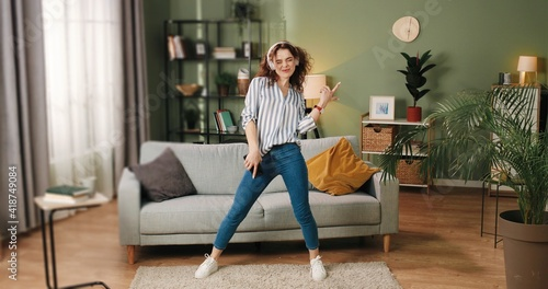 Happy joyful young Caucasian beautiful woman in positive mood dancing moving rhythmically and jumping while listening to music song in headphones on smartphone, having fun in room, leisure concept