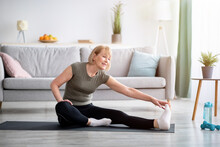 Home Workout. Sporty Senior Lady Stretching Her Leg On Yoga Mat In Living Room, Copy Space