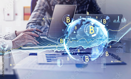 Two businesspeople work together using laptops in modern office to analyze bitcoin market to make best investment decision. Double exposure. Concept of success in cryptocurrency.