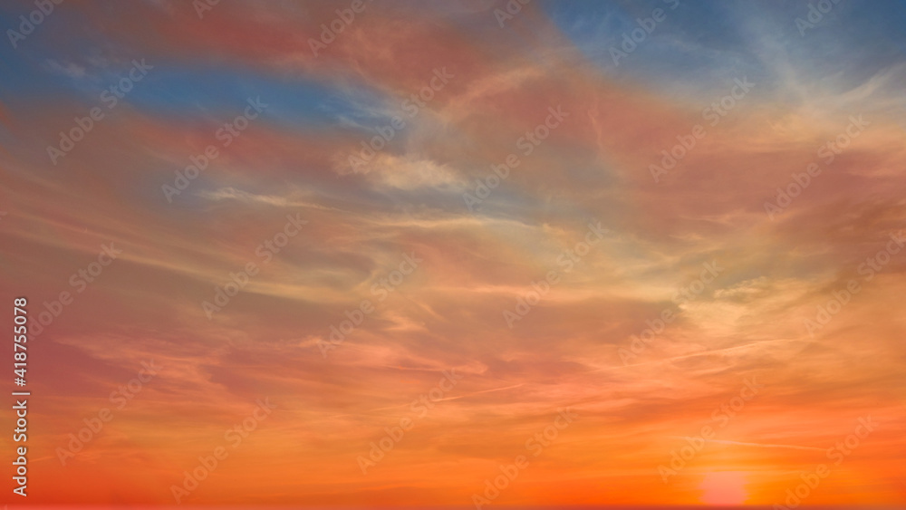 Fototapeta Colorful sunset during golden hour with pastel colors and white clouds.  Some of the blue sky is visible.