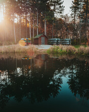 Stacked Canoes Around A Shed On The Edge Of A Pond With Dreamy Pond Reflections As The Sun Shines Through The Pine Trees At Jester Park In Iowa, USA.