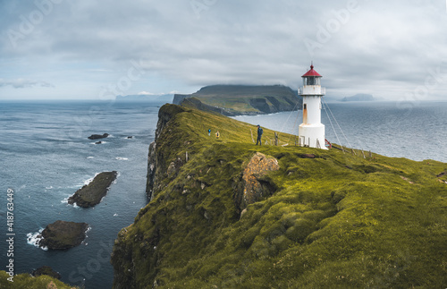 Foto View Towards Lighthouse on the island of Mykines Holmur, Faroe Islandson a cloudy day with view towards Atlantic Ocean