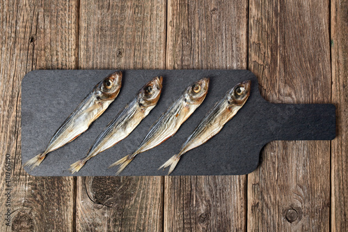 Fototapeta salted scad fish on a black shale stand on a wooden background top view
