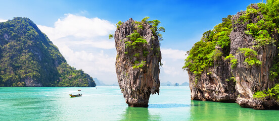 Travel photo of James Bond island with thai traditional wooden longtail boat in Phang Nga bay, Thailand.