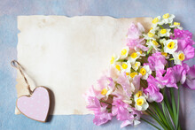 A Bouquet Of Flowers Of Sweet Peas And Daffodils, Paper For The Text Of Congratulations And The Decor Of A Pink Heart.