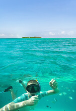 Beautiful Underwater View Of A Young Man Snorkeling Of Lone Small Island Above The Water Surface In Turquoise Waters Of Tropical Ocean.