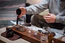 The Process Of Tea Ceremony At Home. The Tea Master Puts Pieces Of Raw Aged Black Tea In A Teapot On A Bamboo Tray