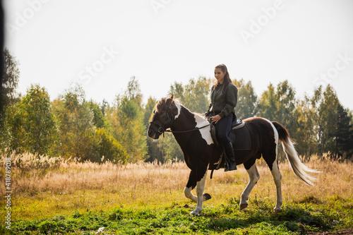 Slika na platnu Cute girl equestrian instructor rides a horse in an equestrian club