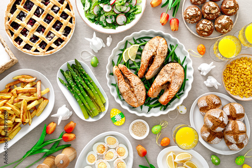 Easter festive table with salmon, asparagus, salad, potato, muffins and berry pie