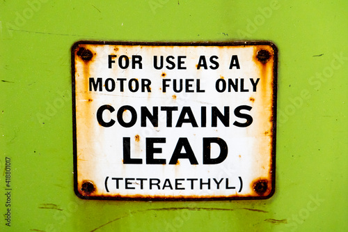 """Leaded gasoline was the primary fuel type produced and sold in America until 1975, as depicted by this sign on an old gas pump (""""contains lead (tetraethyl))."""