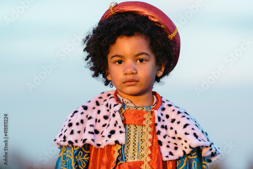 Fototapeta Black child with afro hair, dressed in a wise man's costume, with a serious expression