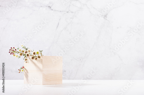 Obraz Wooden cube podium with twig of white spring flowers in white and grey marble interior with sun light and shadow. Showcase for cosmetics, products. - fototapety do salonu