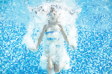 Child Swims In Swimming Pool Underwater, Happy Active Girl Jumps, Dives And Has Fun Under Water, Kids Fitness And Sport On Family Vacation