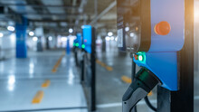 Blurred Electric Car Charging Station For Charge EV Battery. Plug For Vehicle With Electric Engine. EV Charger. Clean Energy. Charging Point At Car Parking Lot. Future Transport Technology.