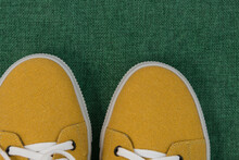 Top View Of Fashionable Mustard-colored Shoes. The Shoes Are On A Green Burlap. The Shoe Fabric Is Made From Recycled Textiles. Eco-friendly Comfort. The Concept Of Caring For The Environment
