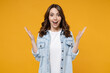 Leinwandbild Motiv Young caucasian surprised shocked overjoyed excited happy brunette woman in casual denim shirt white t-shirt spreading hands isolated on yellow background studio portrait. People lifestyle concept.