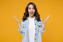 Young Caucasian Surprised Shocked Overjoyed Excited Happy Brunette Woman In Casual Denim Shirt White T-shirt Spreading Hands Isolated On Yellow Background Studio Portrait. People Lifestyle Concept.