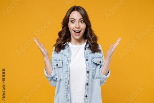 Fotografía Young caucasian surprised shocked overjoyed excited happy brunette woman in casual denim shirt white t-shirt spreading hands isolated on yellow background studio portrait
