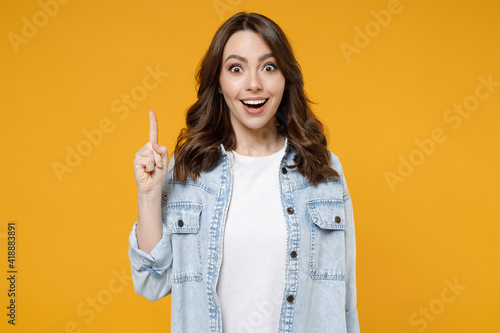 Obraz Young caucasian insighted smart proactive excited happy brunette woman 20s in stylish denim shirt white t-shirt hold index finger up with great new idea isolated on yellow background studio portrait. - fototapety do salonu