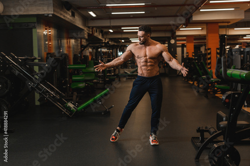 Fotografia a male athlete with a naked torso, abs and pumped-up muscles stands in the gym with his arms spread out to the side