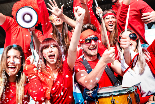 Fotografia Football supporter fans cheering with confetti watching soccer match cup at stad