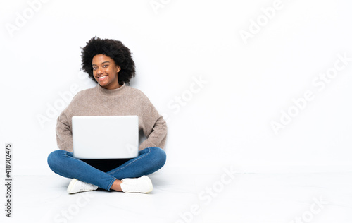 Obraz Young African American woman with a laptop sitting on the floor laughing - fototapety do salonu