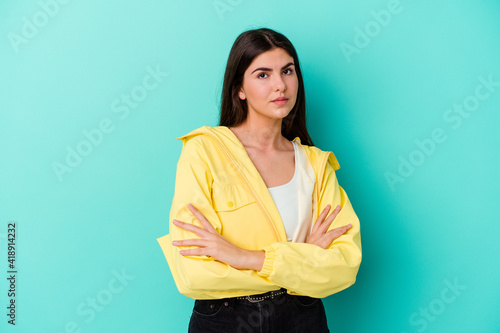 Fototapety, obrazy: Young caucasian woman isolated on blue background suspicious, uncertain, examining you.