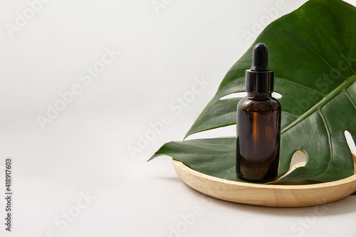 Amber glass cosmetic bottle with green leaf on white background Fotobehang