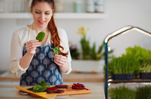 Woman Making Spinach And Beetroot Raw Salad At The Kitchen With Micro Green Cultivation On Background, Healthy Vegan Organic Nutrition