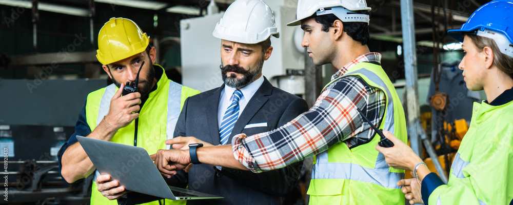 Fototapeta Engineer manager in suite with white helmet checking on laptop order working and planning with engineering team in factory, industry development and technology concept