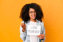 Young African American Curly Woman Holding A Love Yourself Placard Pointing With Finger At You As If Inviting Come Closer.